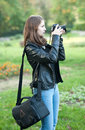 Attractive young girl taking pictures outdoors. Cute teenage girl in blue jeans and black leather jacket taking photos in park Royalty Free Stock Photo