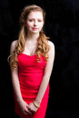 Attractive young girl wearing red dress on black Royalty Free Stock Photos