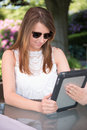 Attractive young girl working in the garden on tablet Stock Images