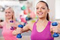 Attractive young girls are training with dumbbells cheerful slim women exercising weights in fitness center they sitting and Royalty Free Stock Photo