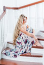 Attractive young lady sitting on the stairs in a long dress Royalty Free Stock Image