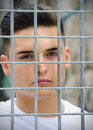 Attractive young man behind metal or steel grid headshot of handsome caged Royalty Free Stock Images