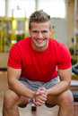 Attractive young man in gym sitting on bench smiling handsome and looking camera Stock Images