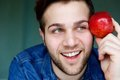Attractive young man holding red apple close up portrait of an and thinking Stock Image