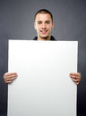 Attractive young man holding white board Stock Photo