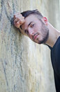 Attractive young man leaning his head against arm on a wall handsome and looking in camera outdoors Stock Photography