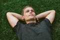 Attractive Young Man Lying with Both Hands Resting Behind his Ne Royalty Free Stock Photo