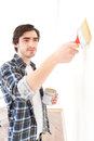 Attractive young man painting a wall in his new flat view of an Stock Photo