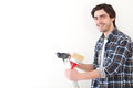 Attractive young man painting a wall in his new flat view of Royalty Free Stock Photography