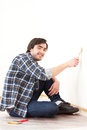 Attractive young man painting a wall in his new flat view of an Royalty Free Stock Photo