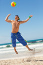 Attractive young man playing volleyball on the beach summertime Royalty Free Stock Photos