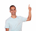 Attractive young man pointing up copyspace portrait of an on blue t shirt on isolated background Stock Photos
