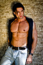 Attractive young man shirtless with jeans leaning against a wall looking to side Stock Photos