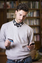 Attractive young man shopping online on mobile phone holding credit card Royalty Free Stock Photos