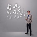 Attractive young man singing and listening to music with musical notes getting out of his mouth Royalty Free Stock Photography