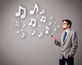 Attractive young man singing and listening to music with musical notes getting out of his mouth Royalty Free Stock Images
