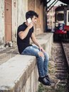 Attractive young man sitting on railroad Royalty Free Stock Photo