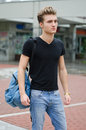 Attractive young man standing in city environment with backsack rucksack on one shoulder Royalty Free Stock Photos