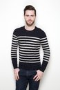 Attractive young man in striped sweater portrait of an posing against white background Stock Photo