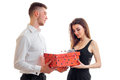 An attractive young man in a white shirt brought cute girl big red gift