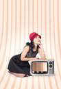 Attractive young pin up lady on television beautiful woman in studio thinking old fashion tv in classic clothes signifying retro Royalty Free Stock Image