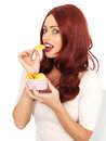 Attractive young red haired woman eating potato crisps with long hair in her twenties looking at the camera and or chips from a Stock Images