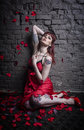 An attractive young red haired woman in a red dress is showered with rose petals she striking dramatic pose against brick Royalty Free Stock Images