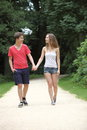 Attractive young teenage couple walking on a date hand in hand along walkway in park smiling at each other as they stroll Royalty Free Stock Images