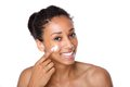 Attractive young woman applying cream on face Royalty Free Stock Photo