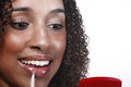 Attractive young woman applying lipgloss an mixed race looks into a hand held mirror whilst lip gloss Royalty Free Stock Photo