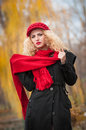 Attractive young woman in a autumn fashion shoot beautiful fashionable young girl with red accessories outdoor cap and scarf the Royalty Free Stock Images