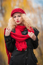 Attractive young woman in a autumn fashion shoot beautiful fashionable young girl with red accessories outdoor cap and scarf the Royalty Free Stock Photo