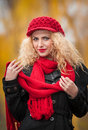 Attractive young woman in a autumn fashion shoot beautiful fashionable young girl with red accessories outdoor cap and scarf the Stock Photo