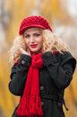 Attractive young woman in a autumn fashion shoot beautiful fashionable young girl with red accessories outdoor cap and scarf the Royalty Free Stock Photography