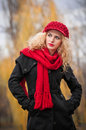 Attractive young woman in a autumn fashion shoot beautiful fashionable young girl with red accessories outdoor cap and scarf the Stock Photography
