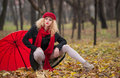 Attractive young woman in a autumn fashion shoot beautiful fashionable young girl with red accessories outdoor umbrella cap and Royalty Free Stock Photos
