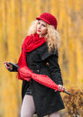 Attractive young woman in a autumn fashion shoot beautiful fashionable young girl with red accessories outdoor umbrella cap and Royalty Free Stock Photo