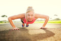 Attractive young woman doing push up sunrise early morning backlit healthy lifestyle sports fitness concept Royalty Free Stock Photography