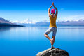 An attractive young woman doing a yoga pose for balance and stretching near the lake high in mountains Royalty Free Stock Photos
