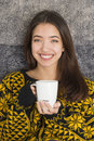Attractive young woman drinking a cup of hot tea beautiful teenage girl at breakfast with white mug steaming Royalty Free Stock Images