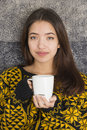 Attractive young woman drinking a cup of hot tea beautiful teenage girl at breakfast with white mug steaming Stock Photography