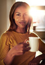 Attractive young woman enjoying a cup of coffee black indoors at home with bright sun flare behind her as she smiles at the camera Stock Photos