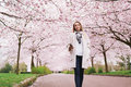 Attractive young woman enjoying music at spring blossom garden beautiful female with mobile phone listening to in park Stock Photo