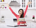 Attractive young woman with gift boxes happy in the kitchen in home Stock Photos