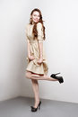 Attractive young woman in golden dress smiles and stands in fashion pose she weares black high heels she has long brown hair Royalty Free Stock Photography