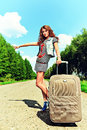Attractive young woman hitchhiking along road Royalty Free Stock Images
