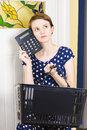Attractive young woman holding grocery basket planning shopping budget while thinking with a calculator to head kitchen background Royalty Free Stock Photos