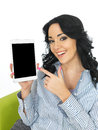 Attractive young woman holding a wireless tablet with long black curly hair and hispanic or european features looking at camera Stock Images