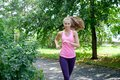 Attractive young woman jogging on park trail. healthy lifestyle concept Royalty Free Stock Photo