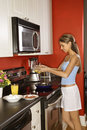 Attractive Young Woman in Kitchen Cooking Breakfas Royalty Free Stock Photography